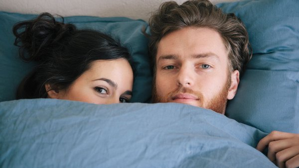 Couple in bed half concealed by sheets