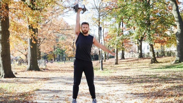 Athlete doing single-arm eccentric push press with dumbbell outdoors