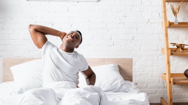 Black man in white T-shirt stretching in bed after waking up