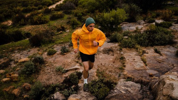 Male trail runner sprinting up rocks on side of mountain
