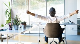 Businessman leaning back and stretching in office chair