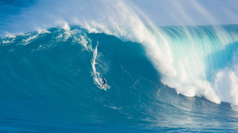 A surfer catches a wave at Jaws.