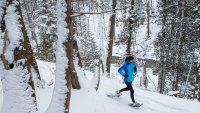 Lone woman in blue jacket running through a forest on snowshoes