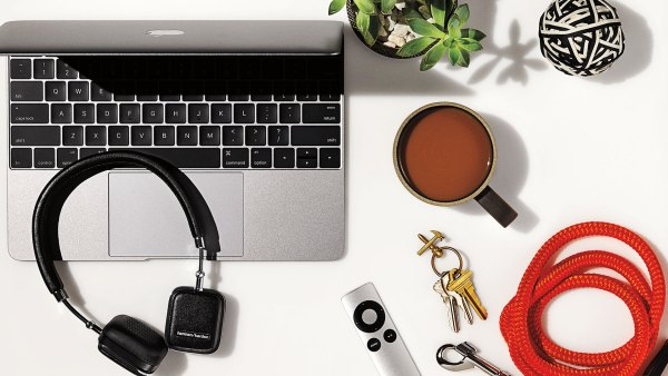 Desktop of laptop, headphones, coffee, Apple TV controller, dog leash, and stress ball