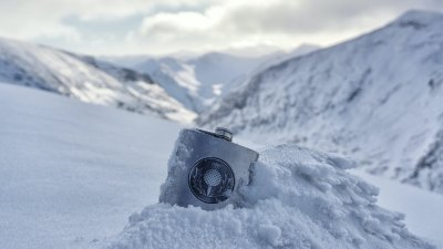Whisky flask in the snow with Nevis Range, Scotland, mountains in the backdrop