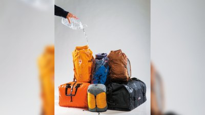 Man pouring water over waterproof dry bags