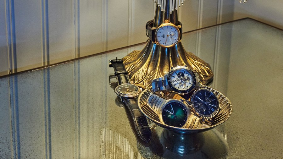 Five luxury watches placed in a bowl and around an antique lamp