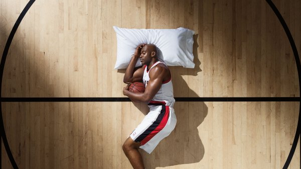 Basketball player sleeping on court with pillow and ball