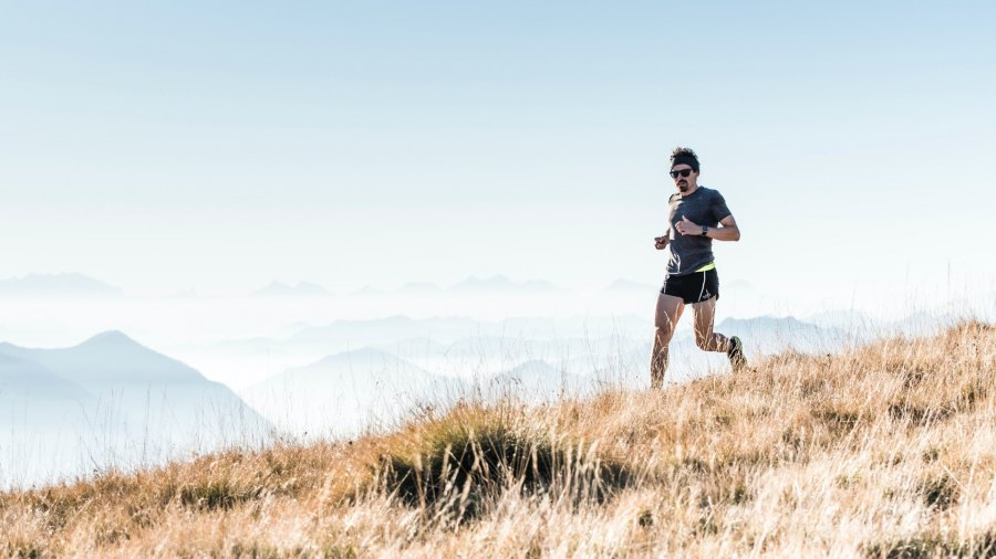 Man running on a grassy hill with mountains in the background