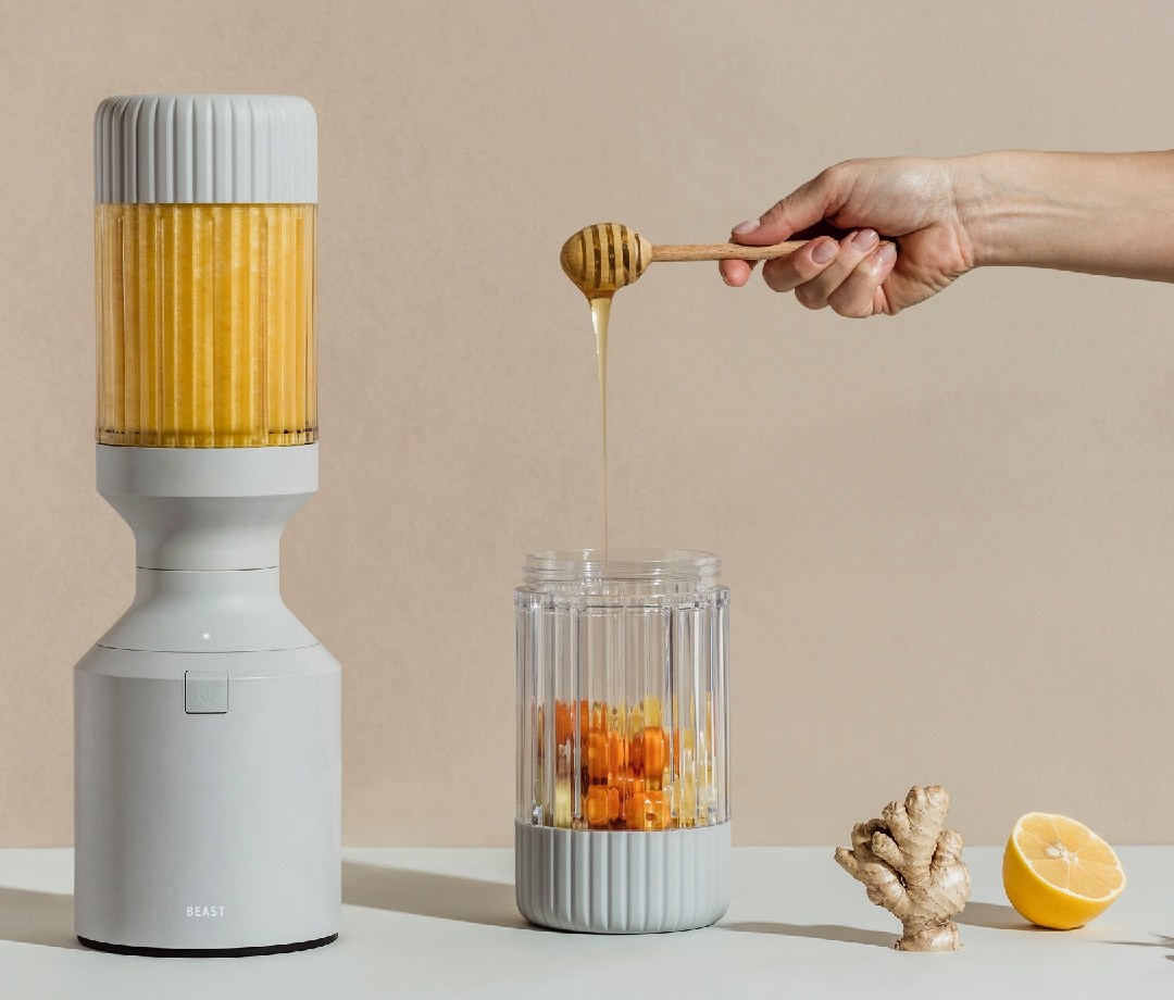 Person drizzling honey into Beast B10+ Health Blender with carrots, lemon, and ginger
