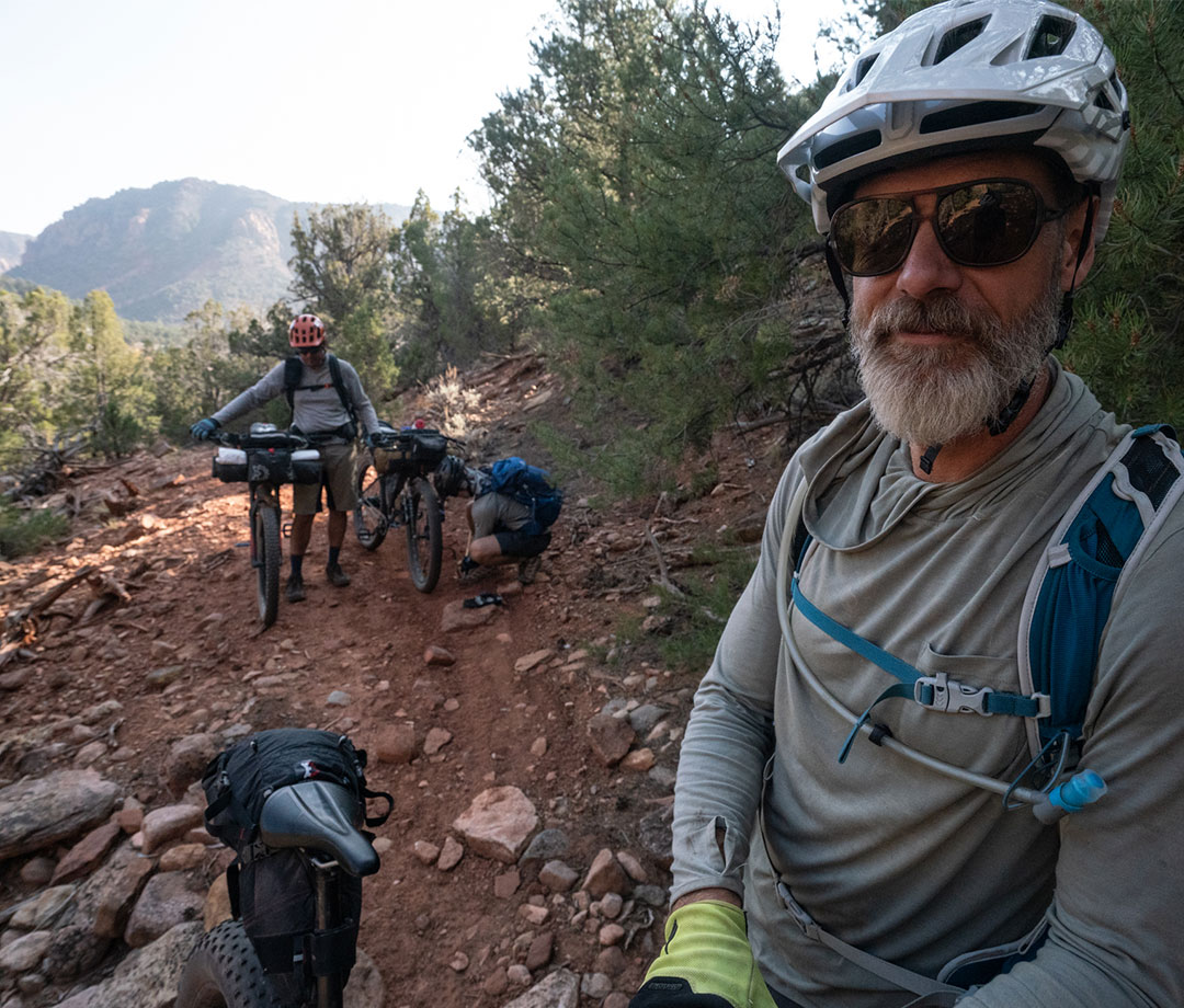 Male mountain bikers pause to catch their breath and make bike adjustmets in desert landscape.