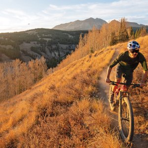 Man riding red mountain bike through mountainous trails
