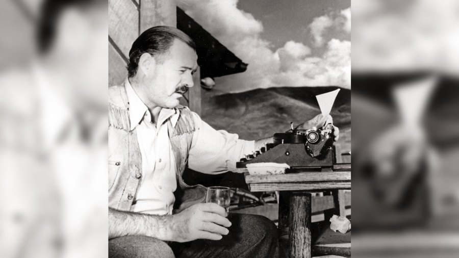 Black and white photo of Ernest Hemingway at typewriter with a drink in hand.