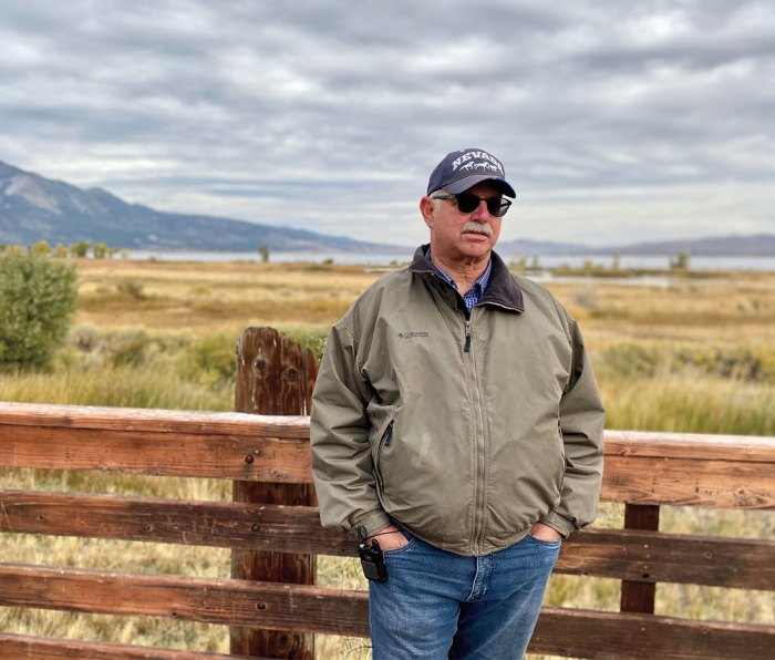 Portrait of conservationist Greg Hendriks against a fence in the countryside