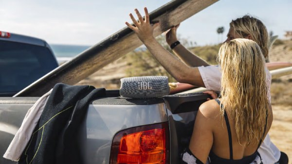 Man and woman pulling surfboard out of a truck's bed with a JBL Charge 5 speaker resting on tailgate
