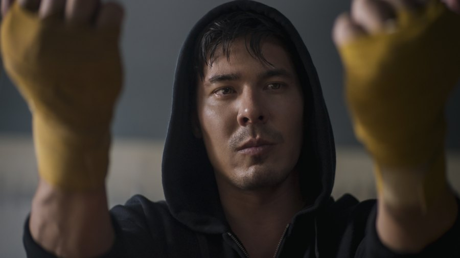 Actor Lewis Tan wearing a hood and hand wraps as part of MMA costume for 'Mortal Kombat' character Cole Young