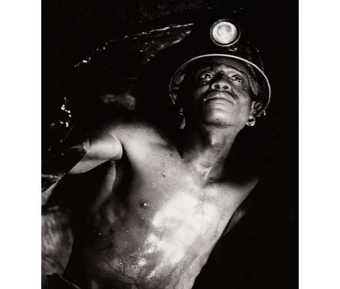 Young South African boy wearing miner's hard hat searching for diamonds