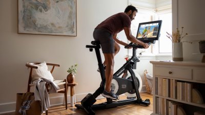 Lifestyle image of a man riding NordicTrack S22i Studio Cycle stationary bike in home