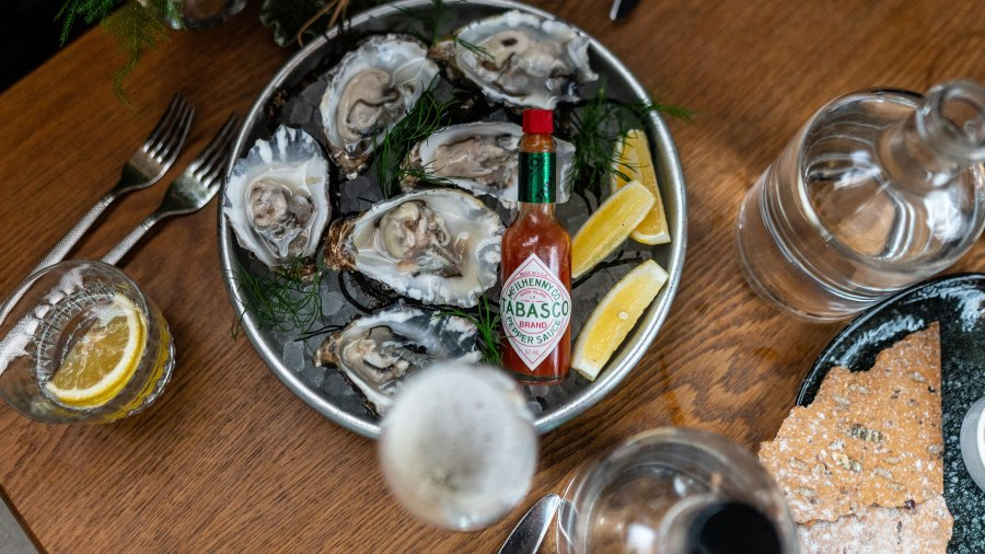 Plate of oysters on ice with Tobasco, lemon slices, and a large cracker