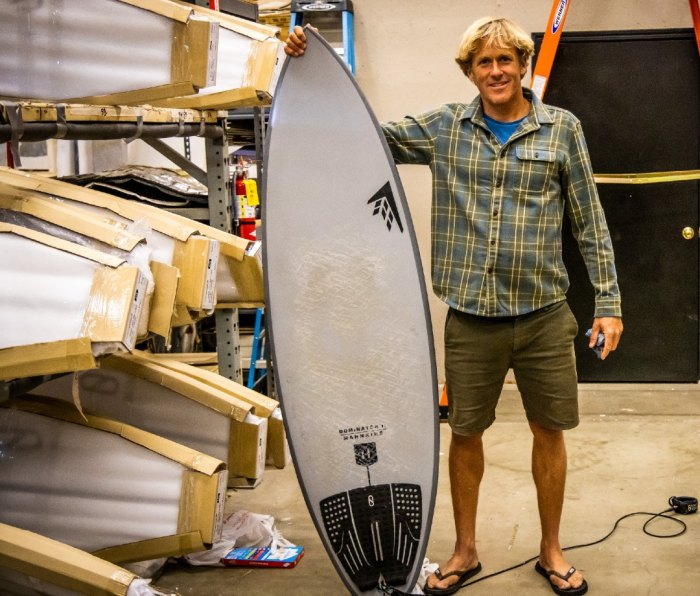 Man holding surfboard in surf shop