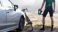 Cyclist standing next to car and bike using Therabody Theragun Promassage device