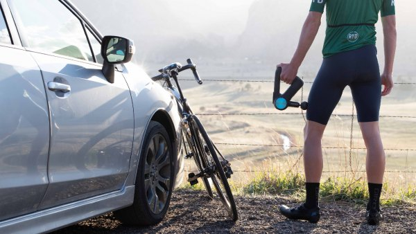 Cyclist standing next to car and bike using Therabody Theragun Pro massage device