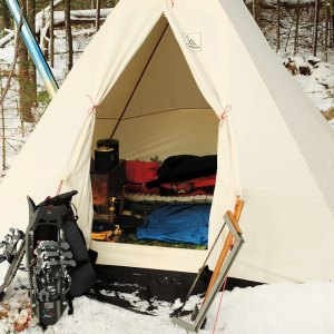 Canvas tent outdoors in the snow with a stove, saw,