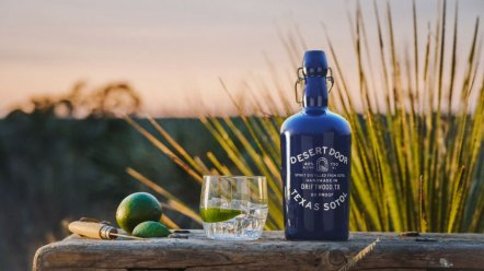 Bottle of Desert Door Texas Sotol next to a glass and limes against the backdrop of Driftwood, Texas.