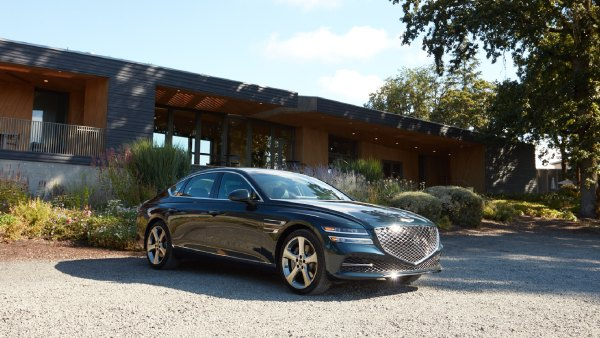 2021 Genesis G80 3.5T car parked outside of a house with clear skies and trees.