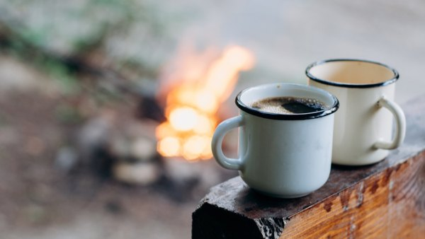 coffee sitting on an old log by an outdoor campfire