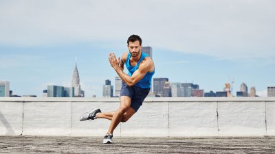 Fit male doing skater exercise on New York City rooftop