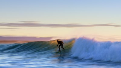 Man surfing in the ocean at sunset