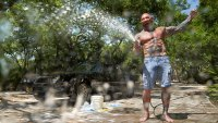Dave Bautista shirtless spraying water from a hose at camera with car in the background