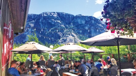 """Patrons at Howe Sound Inn & Brewing sit beneath """"The Chief""""—one of"""