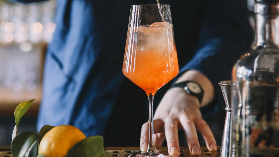 Bartender mixing prosecco into wine glass with oranges