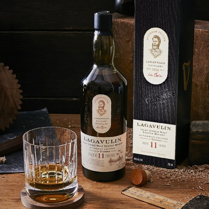 Glass of Offerman Edition: Guinness Cask Finish whiskey next to bottle and box