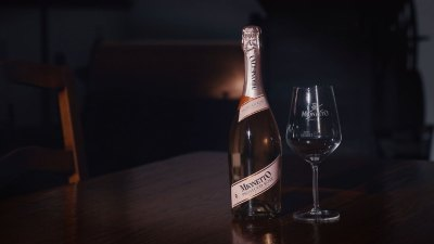 Bottle of Mionetto Prosecco Rosé DOC and empty wine glass on table