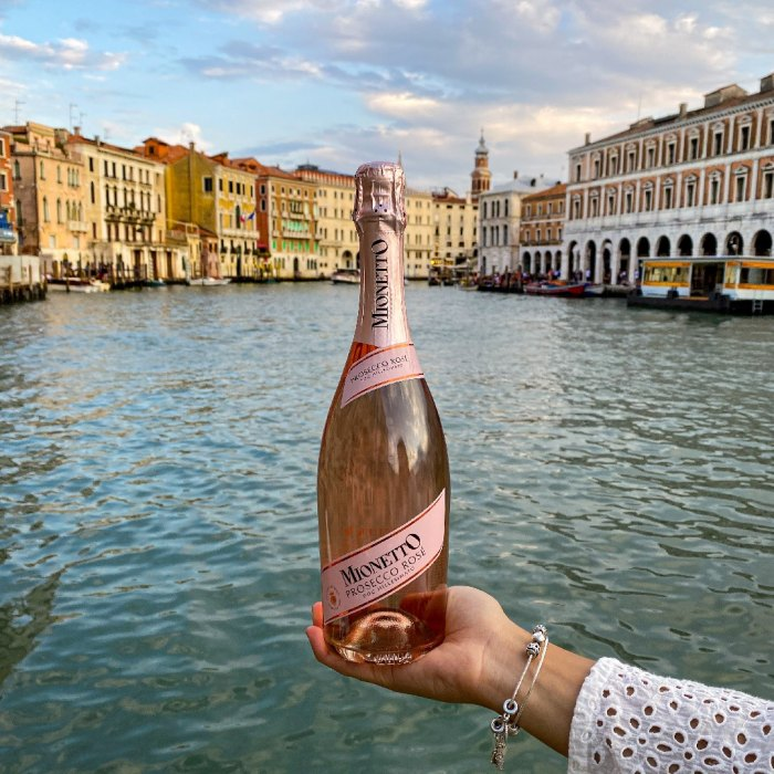 Woman holding bottle of Mionetto Prosecco Rosé DOC in front of canal in Venice