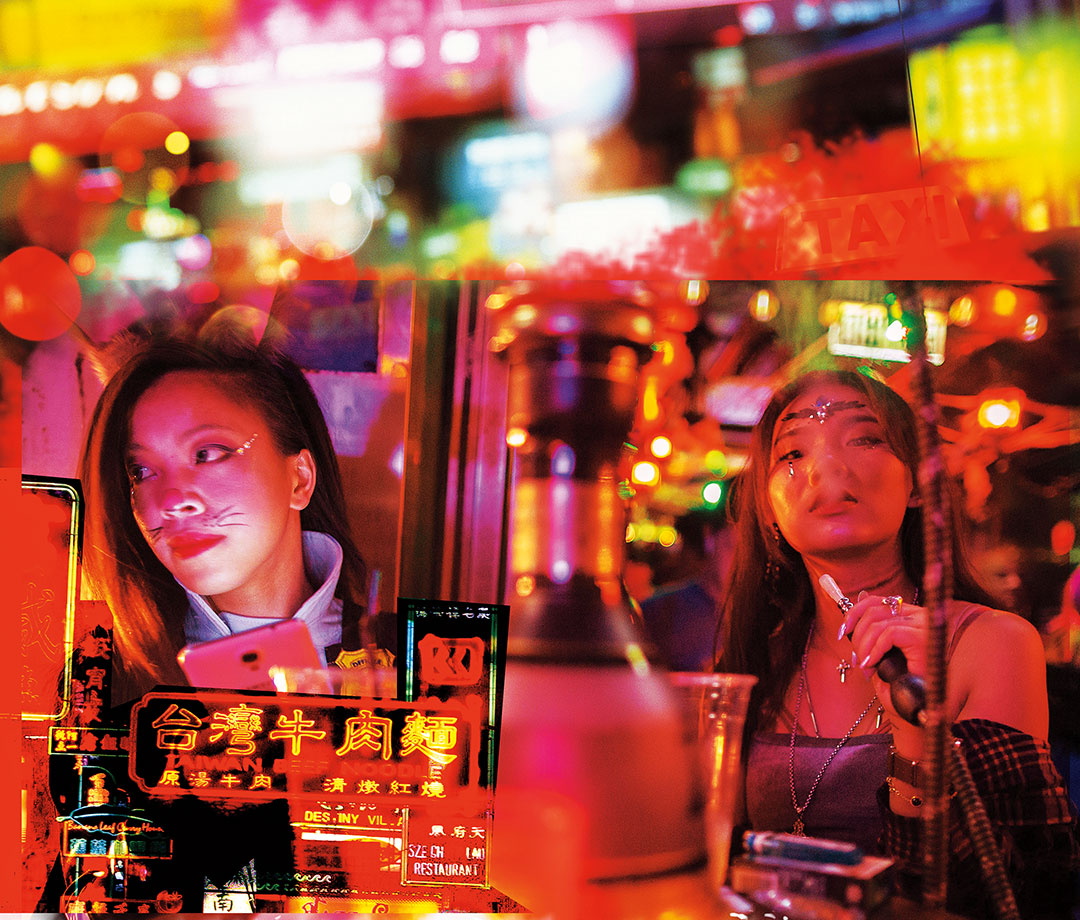 Women smoking at table with neon lights in background