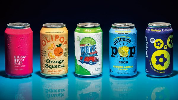 Lineup of colorful soda cans against blue and black backdrop