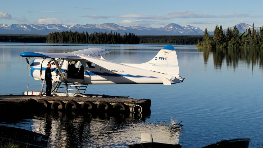 Beaver aircraft on dock with Alaskan mountain range in the distance