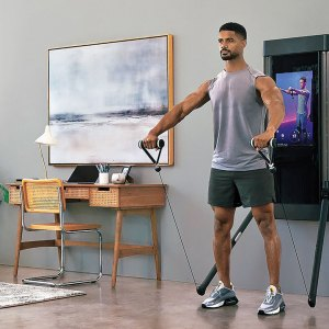 Man exercising at home with Tonal smart fitness device