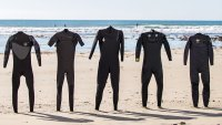 Lineup of wetsuits on beach