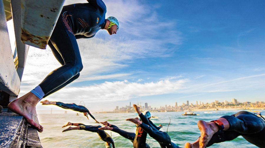 Swimmers diving into the water of The Escape From Alcatraz Triathlon