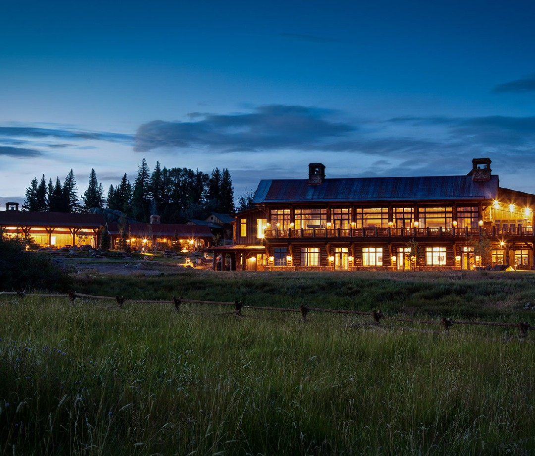 A nighttime view of The Lodge & Spa at Brush Creek Ranch. Tall grass is in the foreground, the lights are all on at the Lodge.