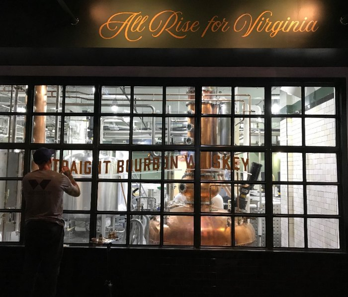 """A man paints the words """"Straight Bourbon Whiskey"""" on the windows of the Tarnished Truth Distilling Company."""