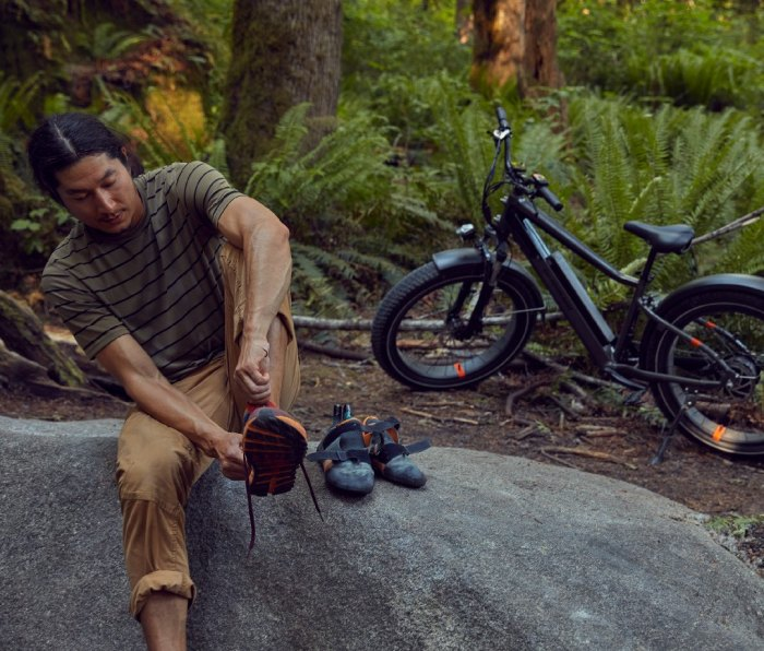 Climber putting rock climbing shoes on with electric fat bike behind him