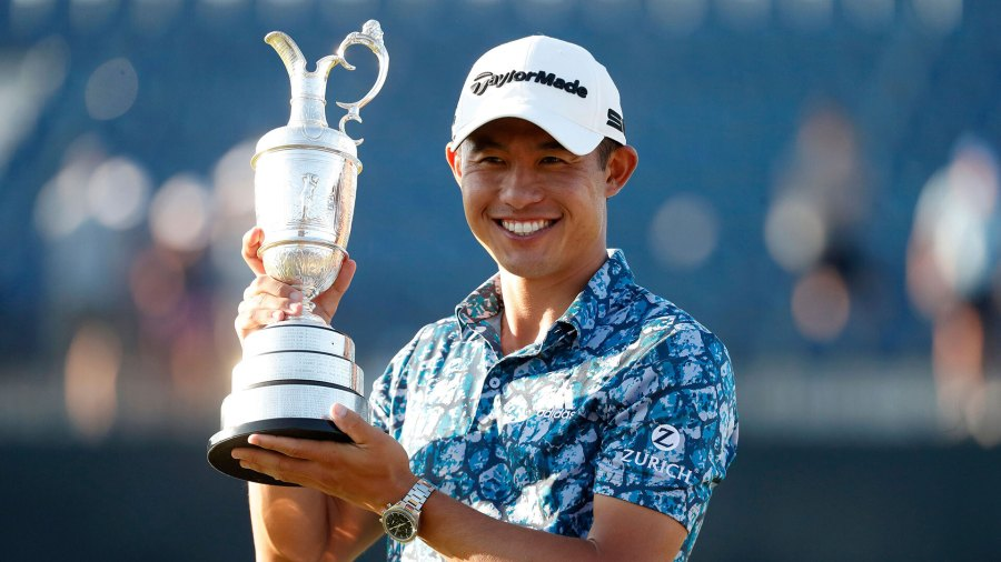 United States' Collin Morikawa holds up the claret jug trophy as he poses for photographers on the 18th green after winning the British Open Golf Championship at Royal St. George's golf course in Sandwich, England.
