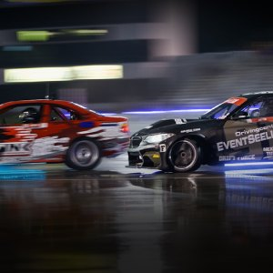 Two Formula DRIFT cars race close to each other at night.