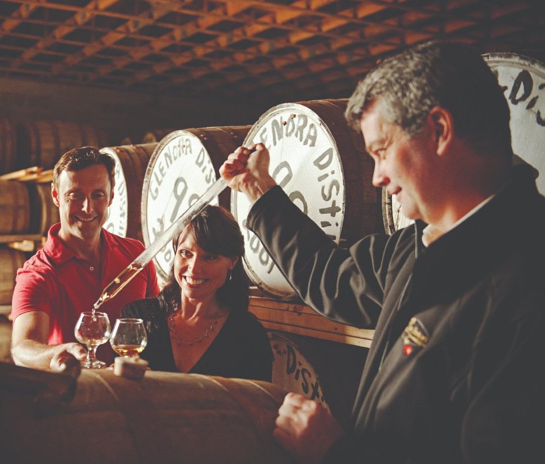 A man gives a couple a sample of Glenora whiskey.